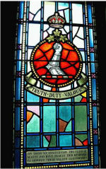 TRUTH DUTY VALOUR – On their 50th anniversary the class of August 1915 at the Royal Military College of Canada have placed this memorial stained glass window to honour their fallen classmates.  841 Lieut Alexis Hannum Helmer (RMC 1912) was the son of Brig. Gen. R. A. Helmer and Elizabeth I. Helmer, of Gilmour St., Ottawa, Ontario. He served with the Canadian Field Artillery, 1st Bde. Early on Sunday morning, May 2, 1915 Lieutenant Helmer left his position to check on a Canadian Battery who had positioned themselves on the bank of the Yser Canal near St. Julien close to the France-Belgium border. He had only gone a few yards when a six inch, high explosive canon shell burst. Lieutenant Helmer was killed in action instantly. He is remembered on the Menin Gate (Ypres) Memorial Belgium.