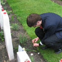 Photo 2 of Adnan Saciragic – Youth Delegate Adnan Saciragic gently sprinkles some soil from PEI on the grave of John Archibald MacLaren in Holten Canadian War Cemetery.