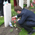 Photo 3 of Adnan Saciragic – Youth Delegate Adnan Saciragic places a Canadian flag on the grave of John Archibald MacLaren in Holten Canadian War Cemetery.