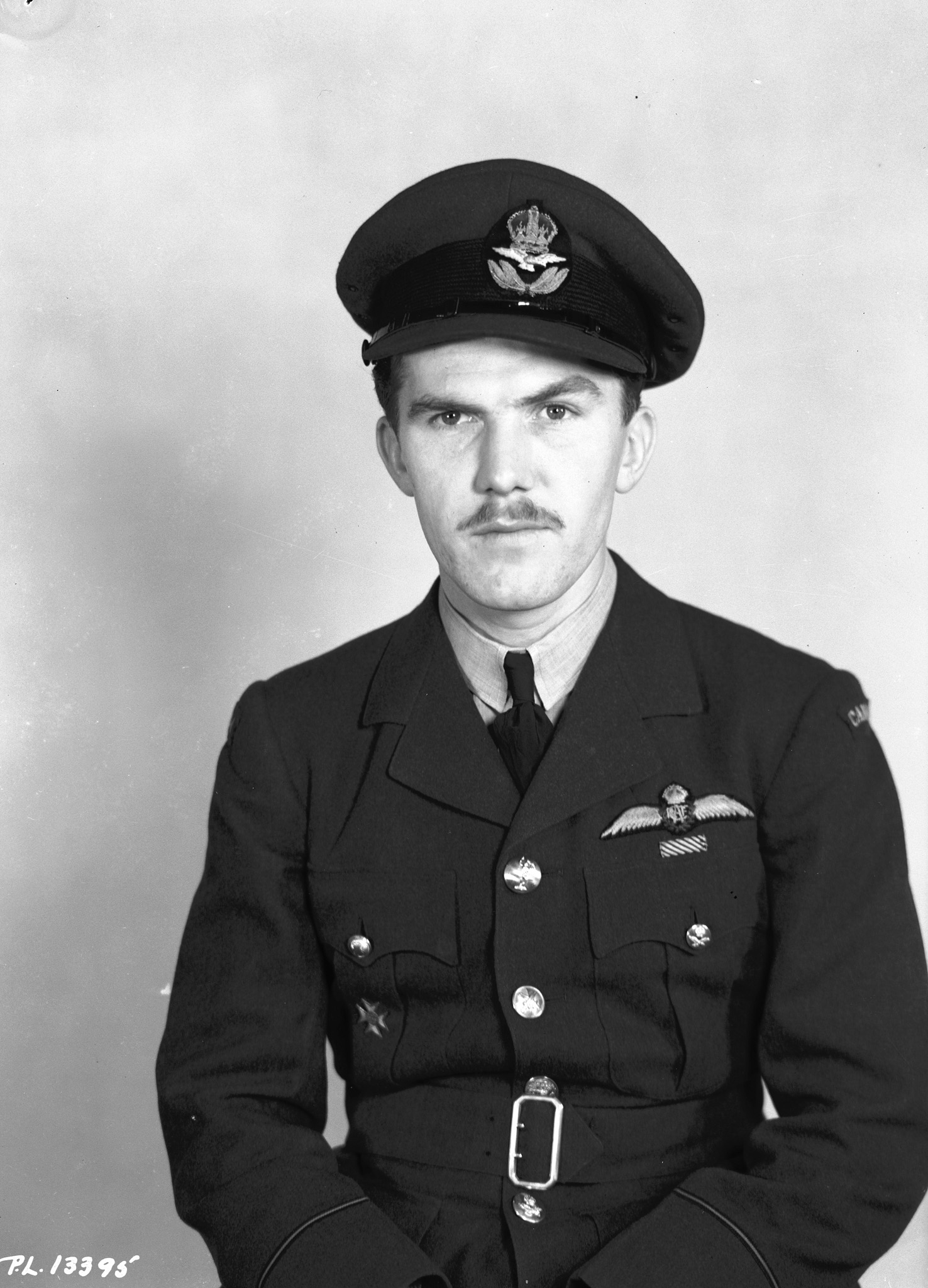 """Photo of James Ballantyne – PL-13395 - 6 March 1943 - Portrait: Pilot Officer J.H. Ballantyne, J/16085, Toronto, Ont. Pilot Officer James Hamilton Ballantyne, D.F.M. of Toronto who won the Distinguished Flying Medal while he was a flight sergeant serving with the Royal Air Force in the defense of Malta. Son of Mr. and Mrs. J.H.H. Ballantyne, 43 Hendrich avenue, Pilot Officer Ballantyne has destroyed at least five enemy aircraft and damaged others and his citation notes that he """"is a most courageous and brave fighter pilot, who has played a worthy part in the defense of Malta."""""""