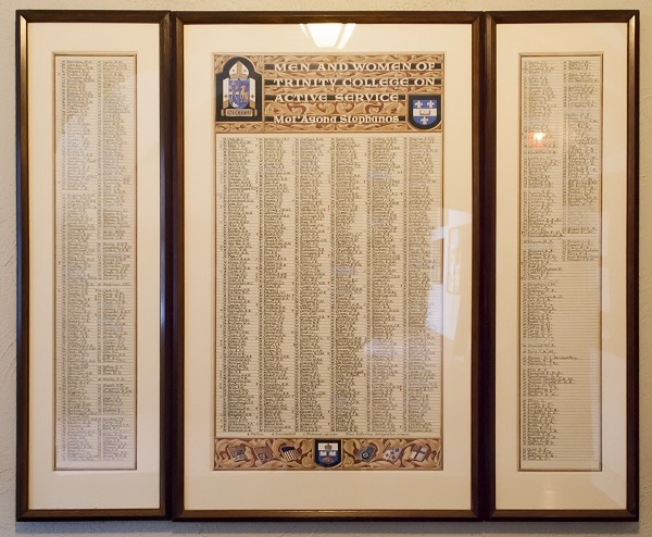 "Memorial Scroll – This framed illuminated scroll, written in calligraphy, is entitled ""Men and Women of Trinity College on Active Service. Met'Agona Stephanos"". It hangs in the hallway outside the narthex of the chapel at Trinity College in the University of Toronto. Small symbols beside the names indicate men and women who are fallen, decorated, and prisoner of war. The list of names includes:  '43 Farrell, D.J. Photo: Cody Gagnon, courtesy of Alumni Relations."