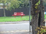 Canadian Bench – A photo of a metal bench erected by the Parish Council. The bench is opposite of the tree split by the Spitfire in the crash. The bench has two maple leaves and it is painted with Canadian colours.   This was erected by the councillors who were attending an exhibition elsewhere, and who decided on the spur of the moment to purchase it in honour of their Canadian hero.