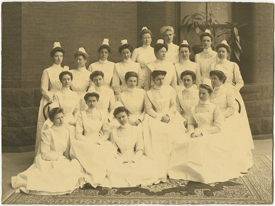 Presbyterian Hospital School of Nursing, class of 1904 – The nurses are standing and sitting outside one of the Presbyterian Hospital buildings.