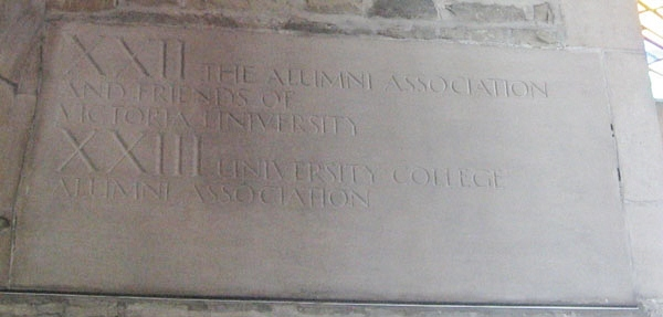 """Inscription – Inscription in Memorial Room, Soldiers' Tower.  The carillon was installed in 1927.  Originally there were 23 bells. Alumni and friends donated funds for bells in memory of those who fell in the Great War. Dedications are carved high on the walls of the Memorial Room, several of which pertain to those who studied at University College. Bell XXIII is dedicated: """"University College Alumni Association"""". The alumnae (female grads) also donated a bell. Photo courtesy of Alumni Relations."""