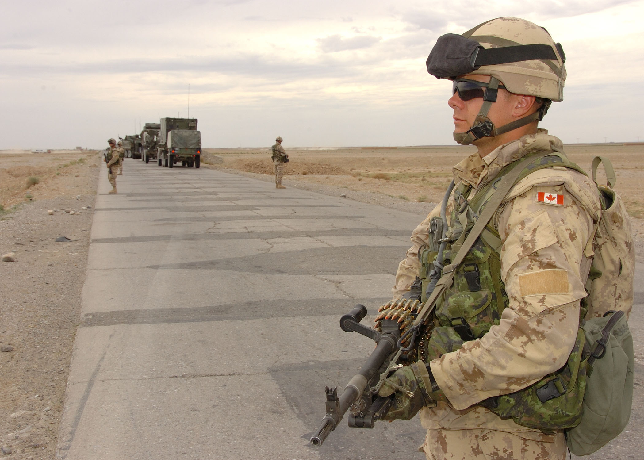 Photo of Bryce Keller – Cpl Bryce Keller 1 Princess Patricia's Canadian Light Infantry (1PPCLI) stands guard outside of a Light Armoured Vehicle (LAV), during a stop while part of a large convoy traveling to a Forward Operating Base (FOB) in the province of Kandahar.
