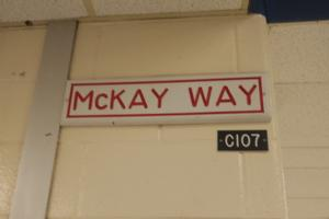 Memorial – Sign in a main hallway in Eastview Secondary School, Barrie, Ontario.  The hallway was named in memory of Private Kevin McKay, who completed his high school education at Eastview.  (Image taken by Gregory J. Barker of Barrie, Ontario, in 2018.)