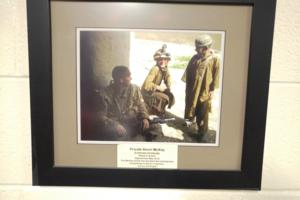 Memorial – A picture, donated by Private McKay's family, on display in the library of Eastview Secondary School, Barrie, Ontario.  It shows Pte McKay chatting with two Afghan boys, while letting one try on his helmet.  (Image taken by Gregory J. Barker of Barrie, Ontario, in 2018.)
