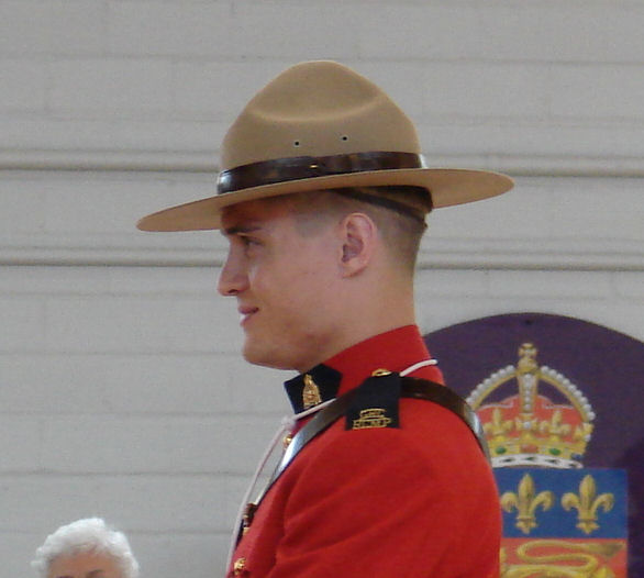 Photo of Adrian Johann Oliver – Adrian being presented his badge by his father, C/Supt Joe Oliver and his identical twin brother, Cst. Benjamin Oliver in June 2009.