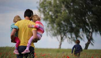 Father holding child in arms while walking in a field of tall grass