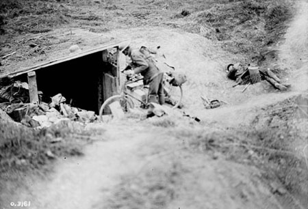 A Canadian cyclist shouting down a dug-out in German for men to come out.  Advance East of Arras.  September, 1918.  Photo: Library and Archives Canada/PA-003071