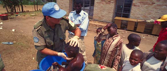 Canadian soldier cleaning a boy in Rwanda.