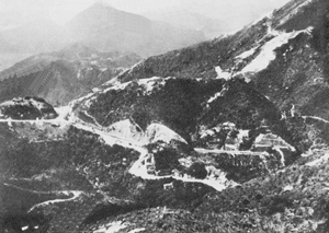 Wong Nei Chong Gap, scene of one of the fiercest encounters in the battle for Hong Kong. Here a company of the Winnipeg Grenadiers held out for several days and inflicted much delay and many casualties upon the Japanese. The Island's main north-south road runs from right to left across the picture. <em>(Canadian War Museum J-2055312)</em>