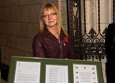 National Memorial (Silver) Cross Mother Patty Braun receives a page from the Books of Remembrance