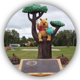 Statue of Winnie-the-Pooh sitting in a tree