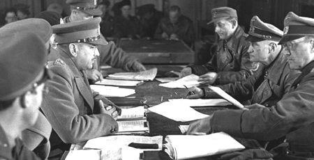 Photo:  Lieutenant-General Charles Foulkes (left centre), <abbr title='General Officer Commanding'>GOC</abbr> 1<sup>st</sup> Canadian forces in the Netherlands receives surrender from General Johannes Blaskowitz.  5 May 1945 / Wageningen, Netherlands.   Photo:  Library and Archives Canada PA 138588