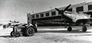 A tractor pulls a Fairey Battle from its hangar