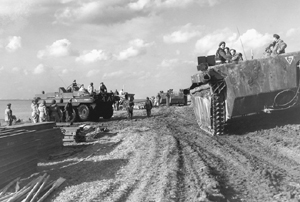 Column of Alligator amphibious vehicles passing Terrapin amphibious vehicles on Scheldt River, October 1944. <em>(Library and Archives Canada PA-114754)</em>