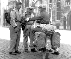Member of Canadian Provost Corps talking to members of the Belgian Resistance, Bruges, September 1944. <em>(Library and Archives Canada PA-116733)</em>